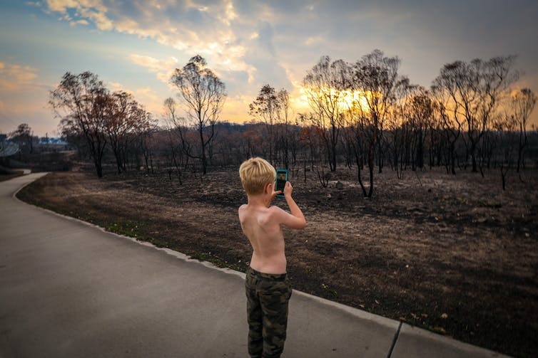 Boy takes photo of burned landscape
