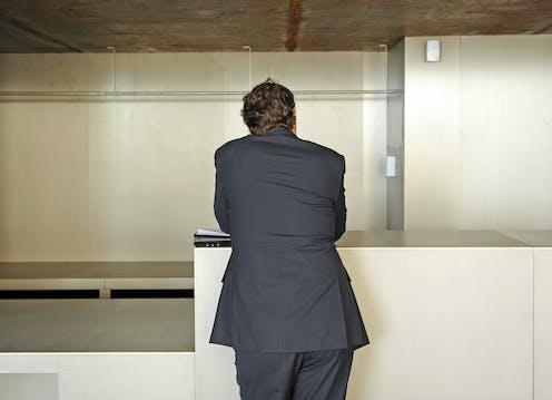 Un hombre de traje, de espaldas, apoyado en un mostrador vacío.
