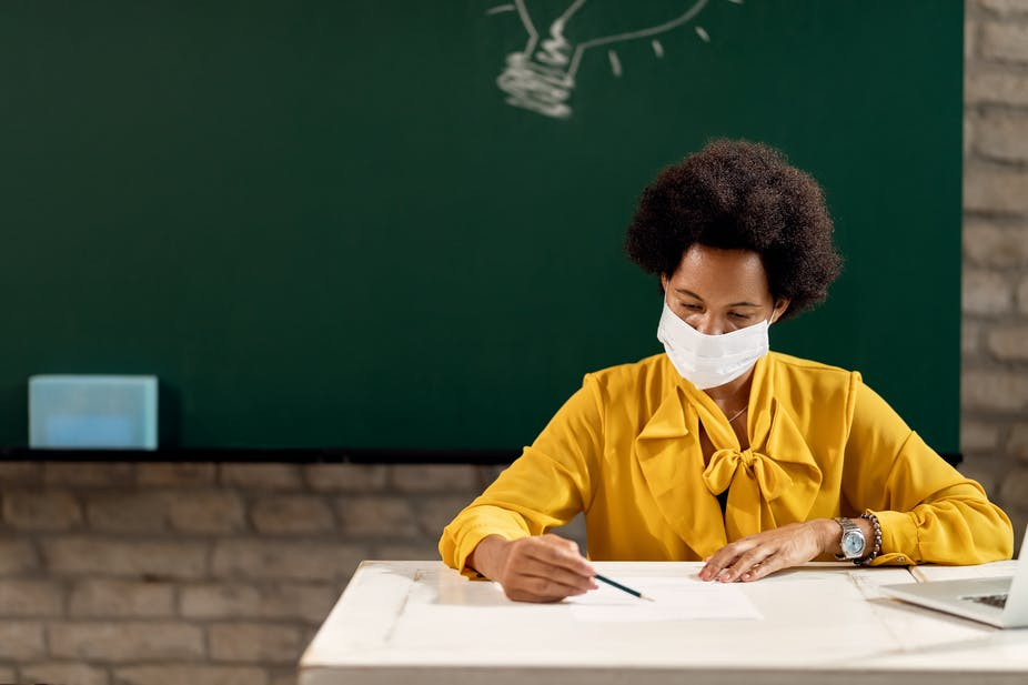 A teacher sitting on her desk with a face mask and a writing board behind her.