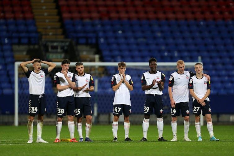 Sept joueurs de football Bolton Wanderers font la queue devant le stade vide.