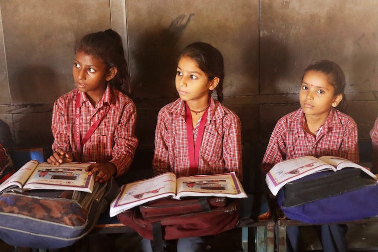 Three schoolgirls sitting at desks with textbooks open.