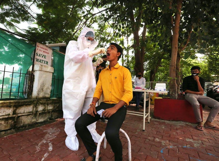 Man sits while medical worker takes coronavirus swab test.