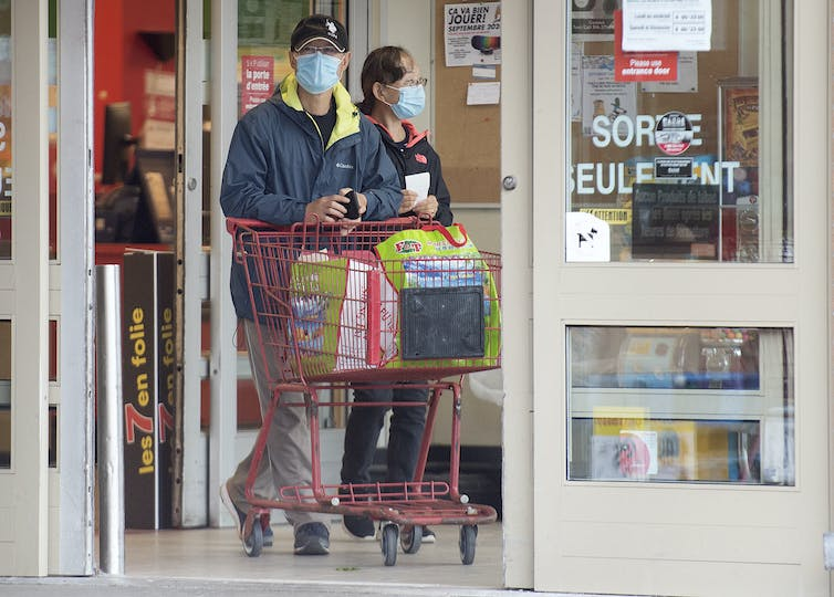 People wear face masks as they leave a grocery store pushing a cart.