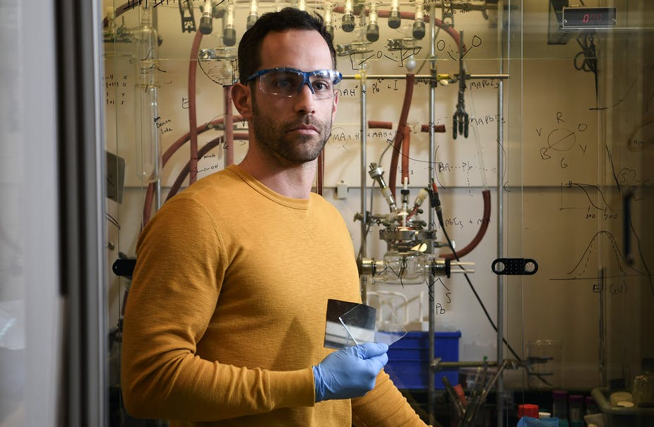 A man in a yellow shirt and blue latex gloves standing in front of a wall of equations holds a clear square of glass.