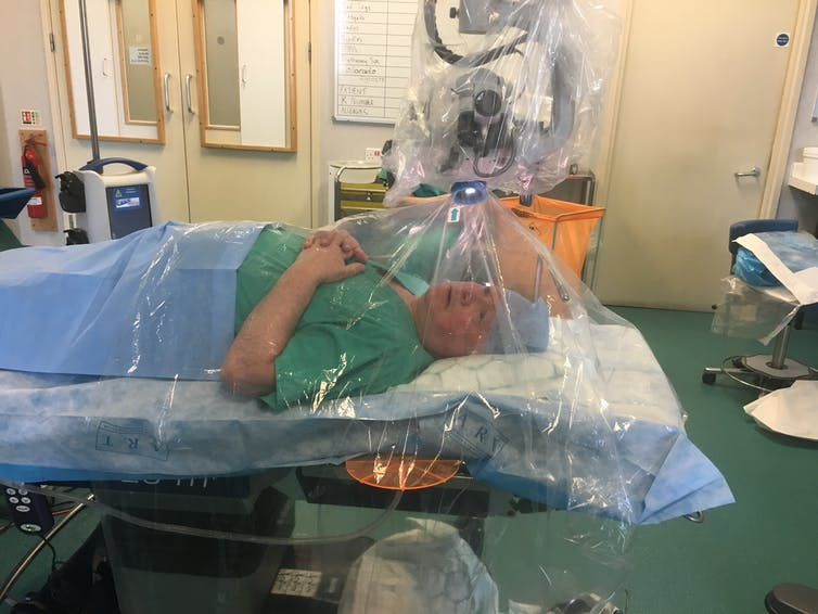 A man in surgical srubs lies on an operating table underneath a transparent plastic tent.