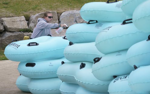 A lifeguard sprays disinfectant on inflatable rafts.
