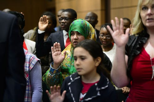 New Canadians take the Oath of Citizenship on Parliament Hill in Ottawa.