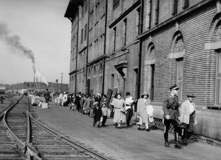 Black & white photo showing people walking past a building. Railroad tracks can be seen on the left of the image.