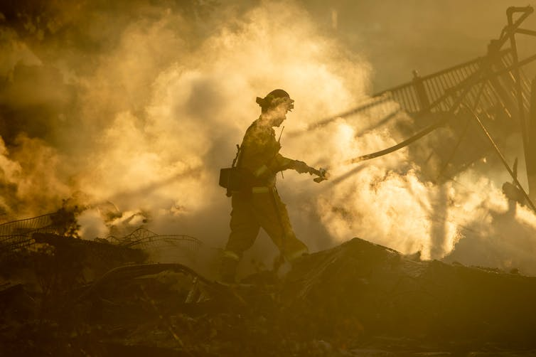 A firefighter walks near the smoldering remains of homes during a fire that reached San Bernadino, California, in 2019.