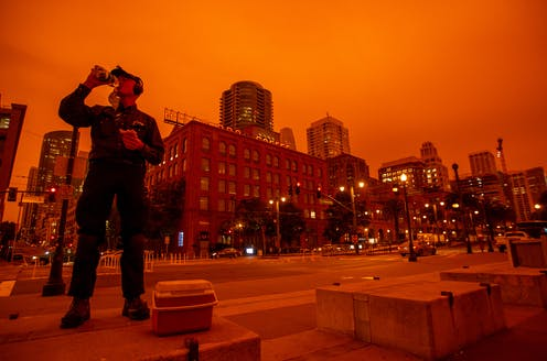 A worker in San Francisco eats lunch under a sky turned orange by wildfire smoke.