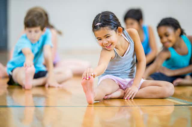 Several children on the floor, stretching.