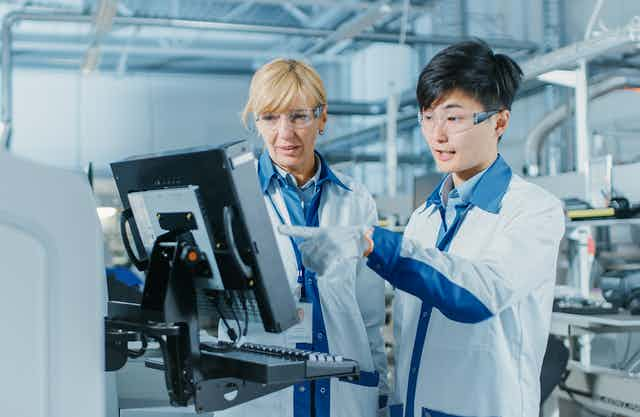Young male engineer talks with female supervisor while looking at computer screen in high-tech factory