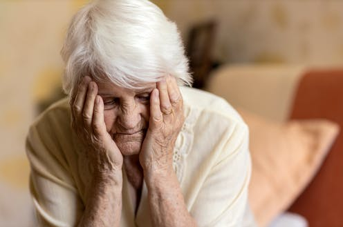 An old woman holds her head in her hands.