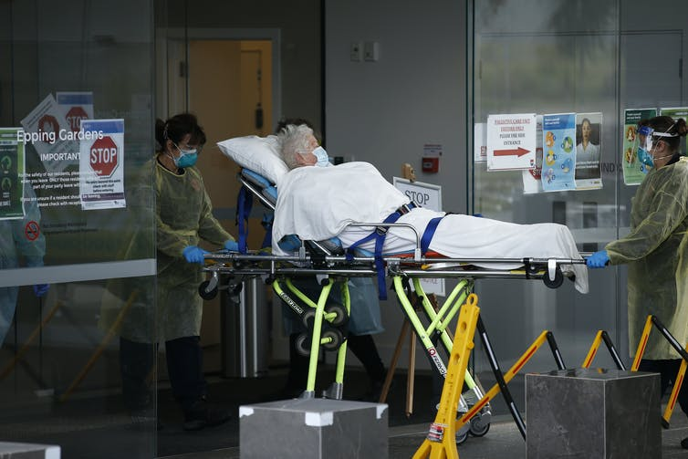 An aged care resident is removed by stretcher from their nursing home.