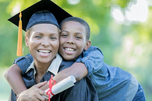 A woman wearing a graduation cap is being hugged by her young son.