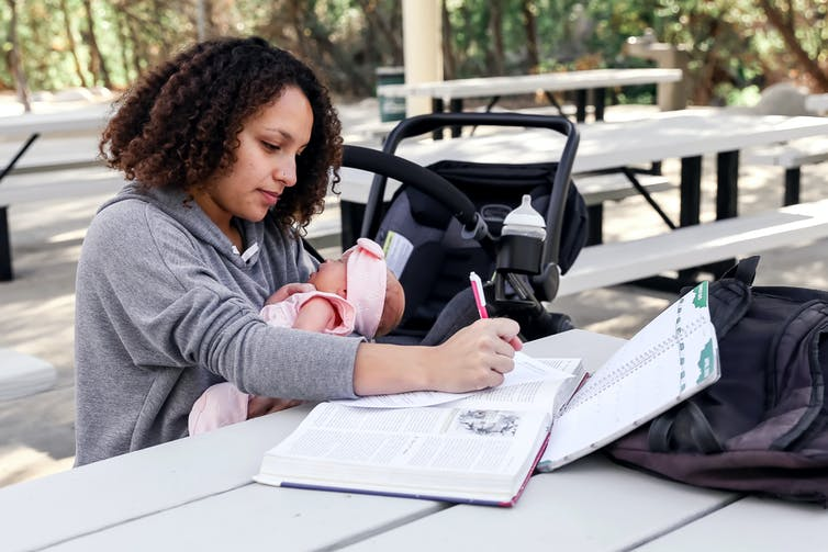 A mother holds a young baby while writing in a book at a table on a college campus.