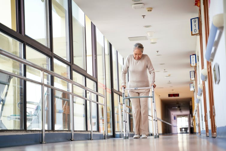 An elderly woman walks down the corridor of a nursing home using a frame.