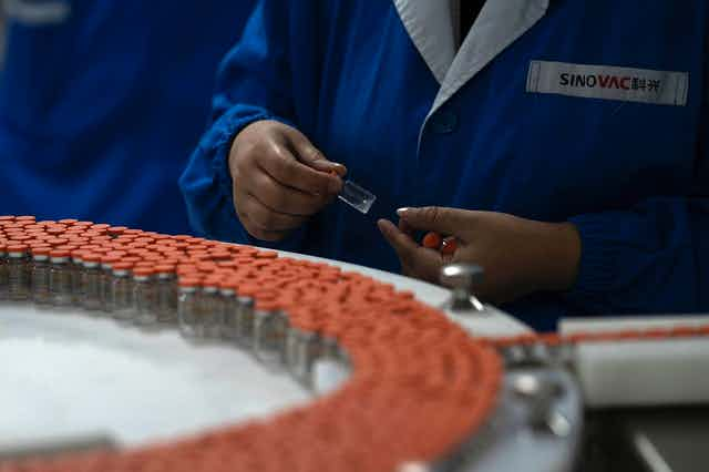 Orange-capped vials on a conveyor belt. A worker holds several vials in their hands.