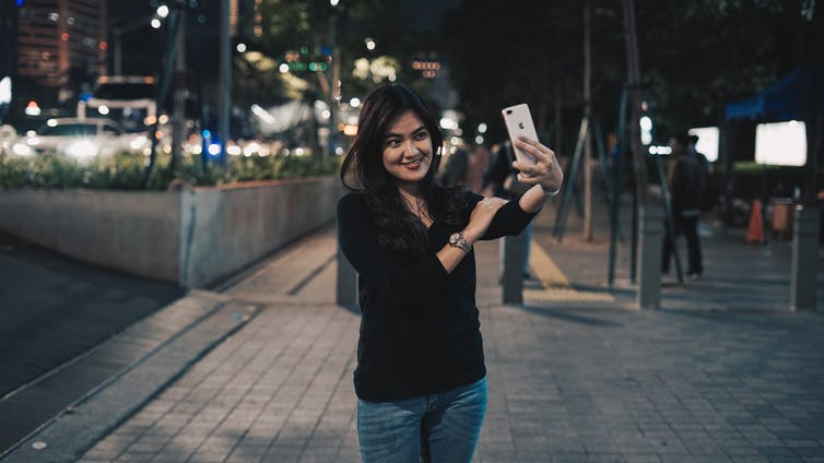 Girl takes selfie on street