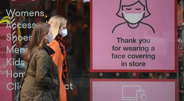 Shoppers wearing face masks pass a COVID-19 awareness sign on a high street in England