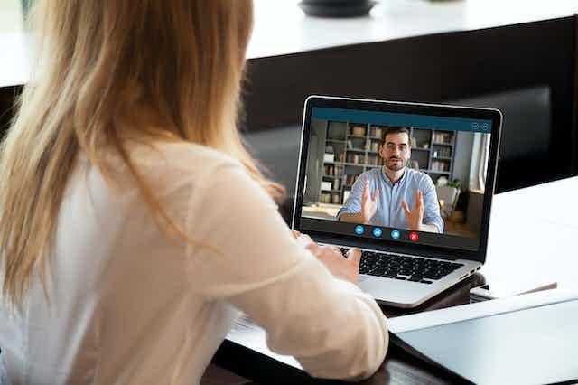 Woman watching video on laptop of man talking