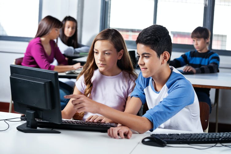 Teenage girl and boy looking at computer screen.