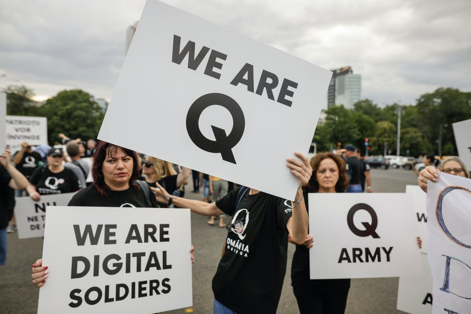People display Qanon messages on cardboard signs at a political rally.