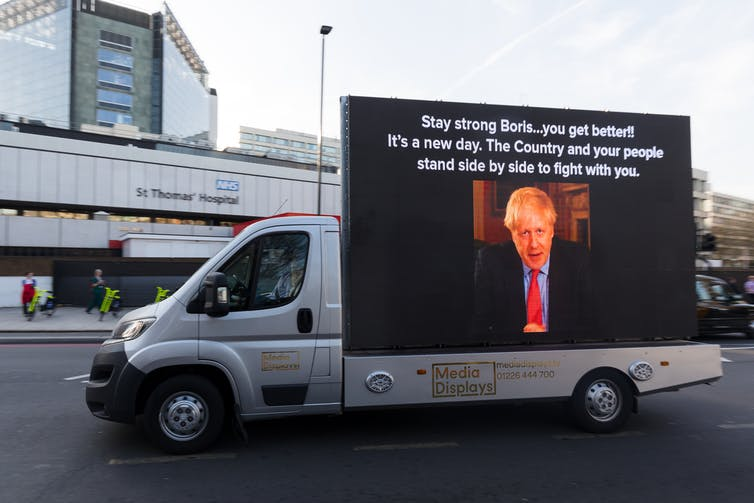 Billboard on a van with a photo of Boris Johnson drive past St Thomas's hospital