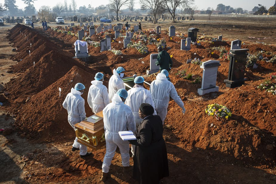 Six men wearing white protective gear carry the coffin of a COVId-19 victim at a cemetery in South Africa