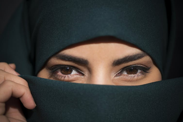 Close up of a woman wearing a niqab, who is clearly smiling.