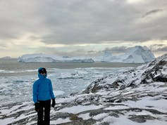 Michalea King, a glacier researcher, stands in front of bay full of icebergs.