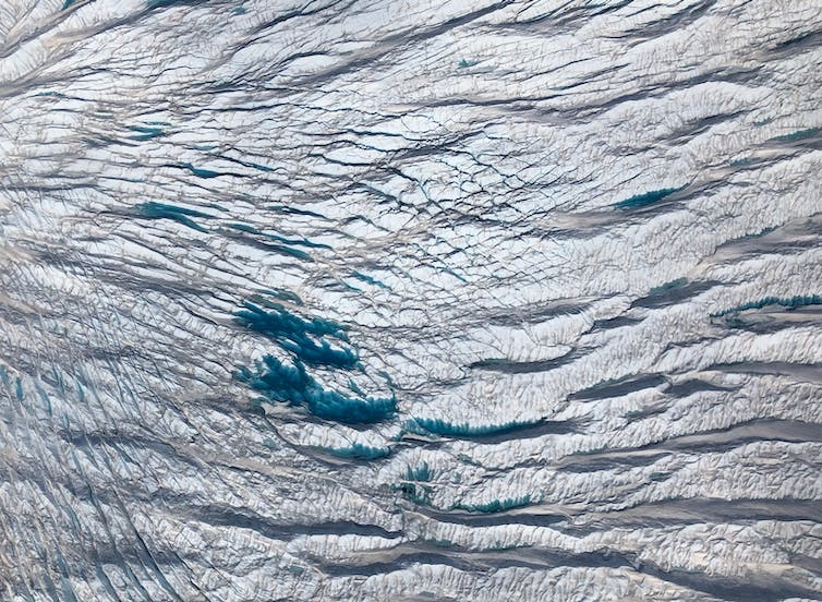 An aerial view of a pond on the top of a glacier formed by melting ice.