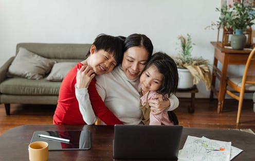 A woman sits at a table embracing her two children, a laptop in front of them.
