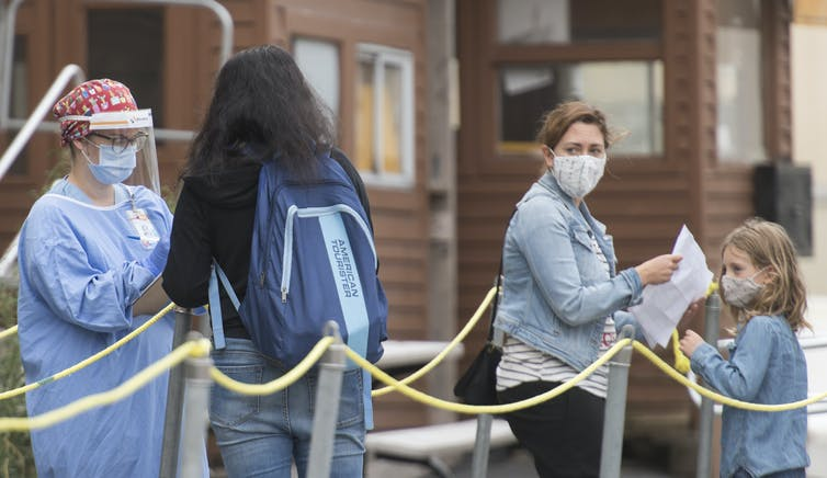 A health-care worker is seen wearing a face visor and other protective equipment as people wait in line to be tested for COVID-19.