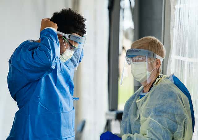 A health-care worker in personal protective equipment secures his visor as another health-care worker in full PPE stands near him.