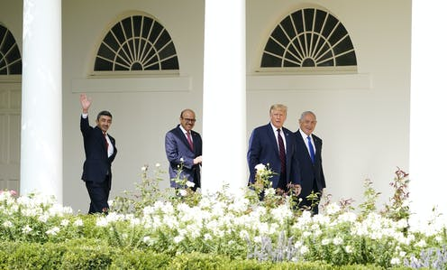 Donald Trump walks to the Abraham Accords signing ceremony at the White House with Israeli Prime Minister Benjamin Netanyahu, Bahrain Foreign Minister Khalid bin Ahmed Al Khalifa and United Arab Emirates Foreign Minister Abdullah bin Zayed al-Nahyan. Shrubs with white flowers are in the foreground.