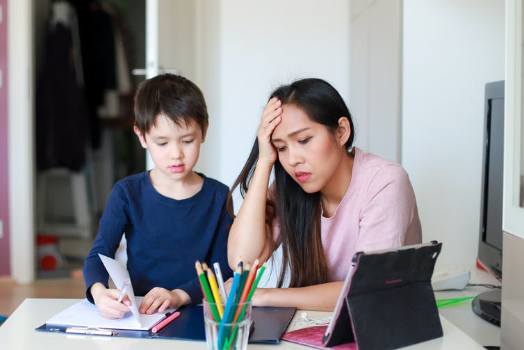 Stressed mother helping her son with school work