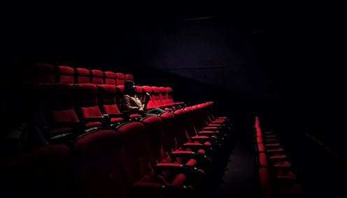 One woman sits in empty theatre