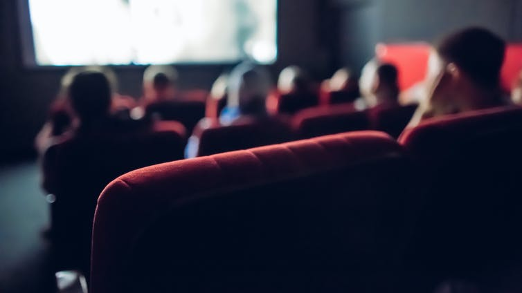 Audience backs in small cinema.