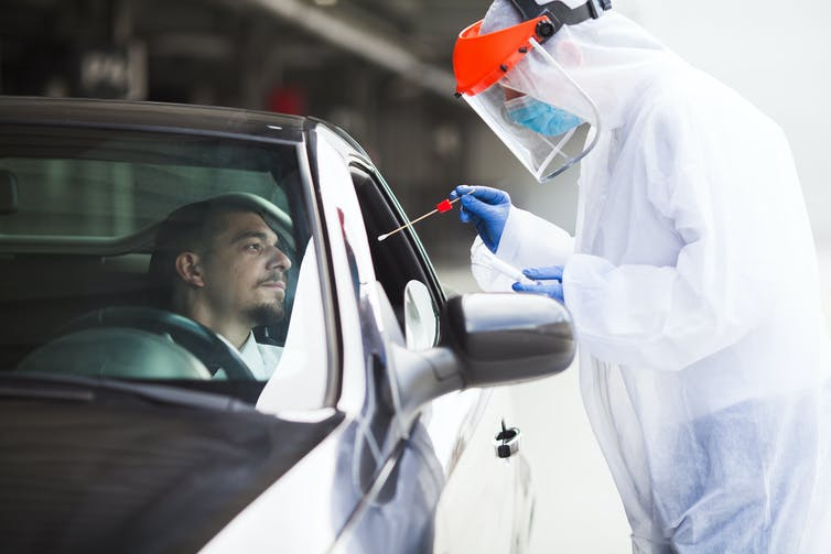A health worker dressed in PPE prepares to take a swab from a man in his car.