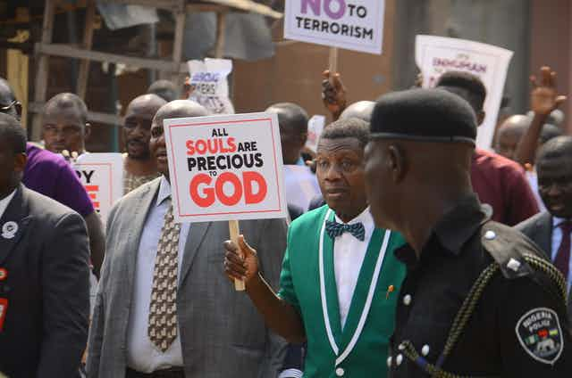 Men walking in the street holding placards