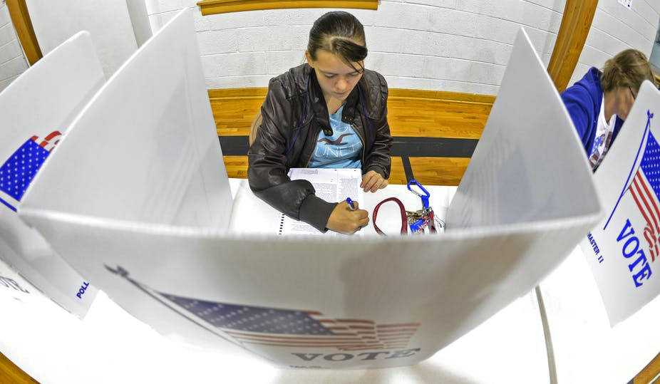 Woman filling in ballot in voting booth