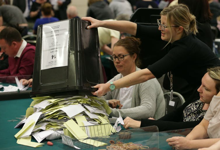 Woman empties container of ballot papers on table in front of other women.