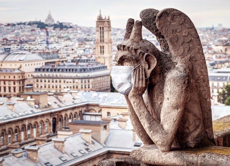 Una de las gárgolas de Notre-Dame (París) con mascarilla.