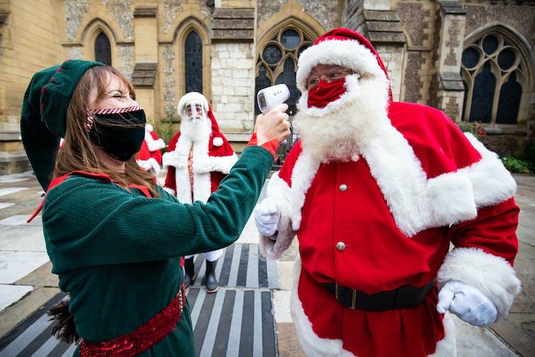 A Christmas Elf checks Santa's temperature as part of festive training.