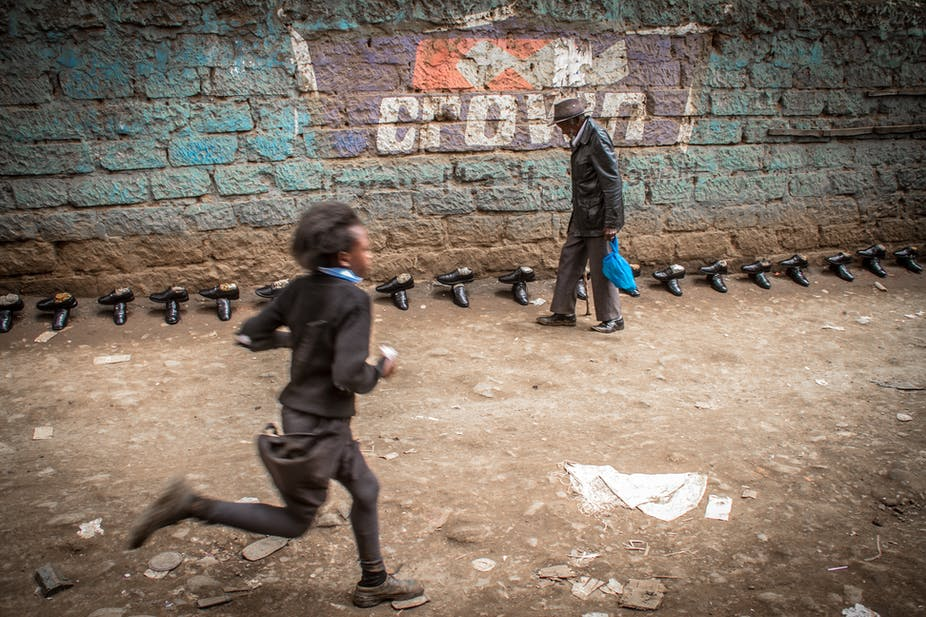 A school girl runs past an old man walking along a street with shoes for sale