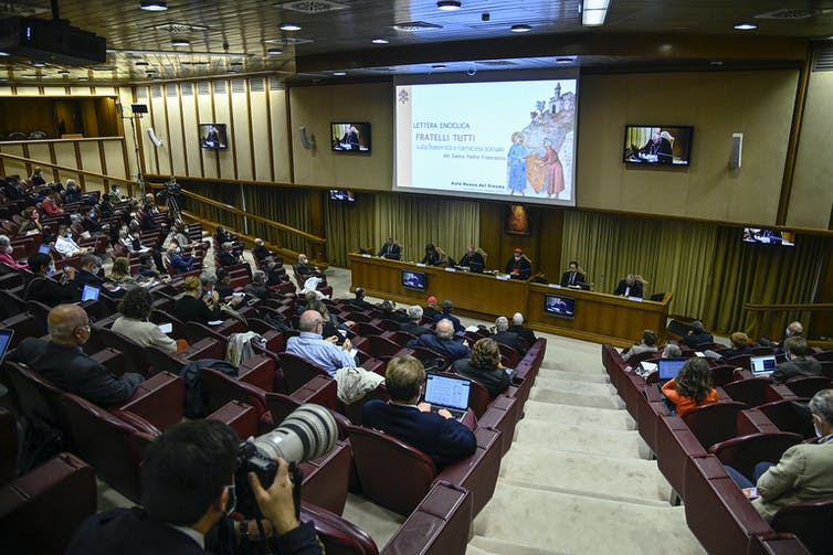 A penal of six people presenting the papal encyclical to a group of people in an auditorium in Rome.