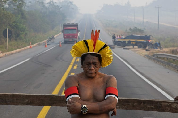 An indigenous man stands in front of a roadblock.