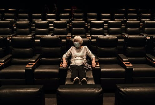 A woman sits in an empty Regal theater in California.