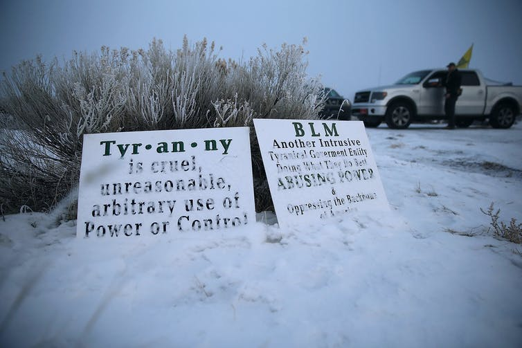 Protest signs in snow with protesters in background.
